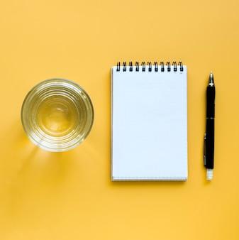 Vista superior del vaso de agua con cuaderno y bolígrafo