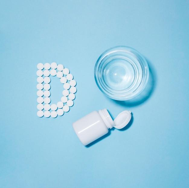 Vista superior del vaso de agua y recipiente con pastillas ortografía letra d