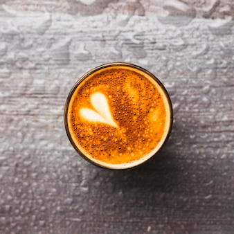 Vista superior del vaso de café sabroso con arte latte sobre fondo gota de agua