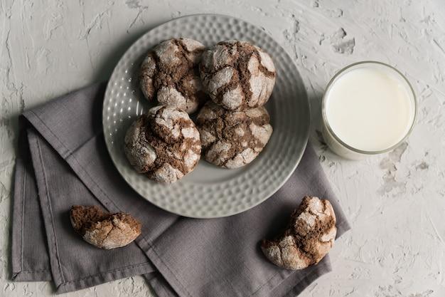 Vista superior del vaso de leche con crujientes galletas de chocolate crujientes. sabroso refrigerio o desayuno.