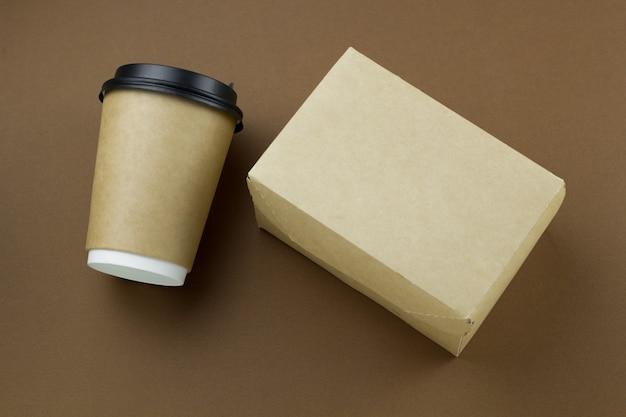 Vista superior del vaso de papel desechable con tapa de plástico y caja de cartón sobre fondo marrón