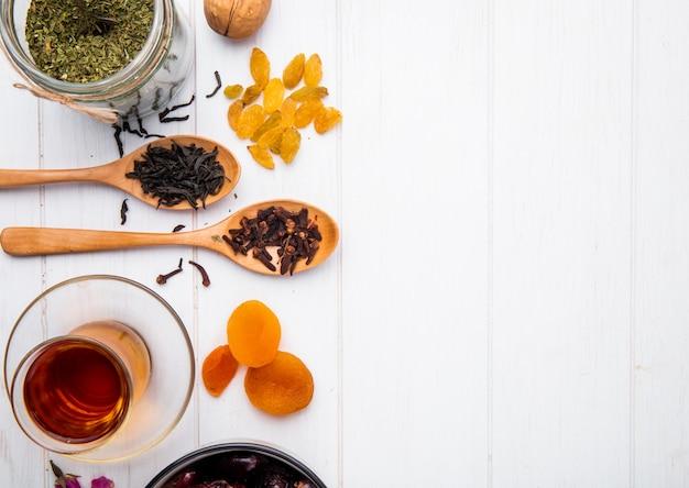 Vista superior del vaso de té armudu con albaricoques secos dulces y pasas y cucharas de madera con hojas secas de té negro y especias de clavo en madera blanca con espacio de copia