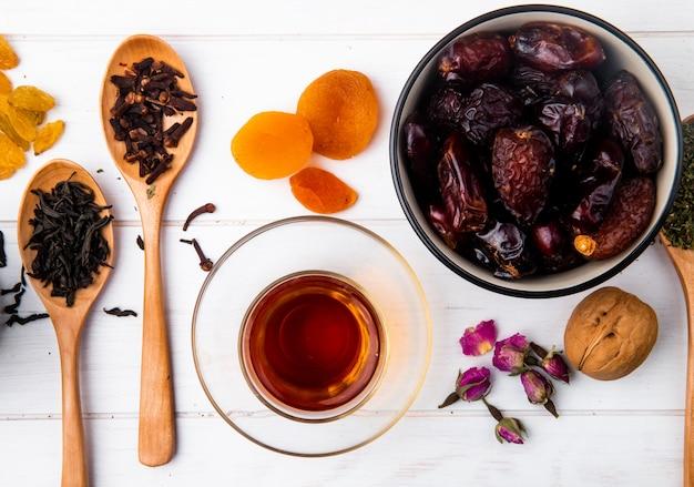 Vista superior del vaso de té armudu con dátiles dulces secos en un tazón y cucharas de madera con hojas secas de té negro y especias de clavo en madera blanca