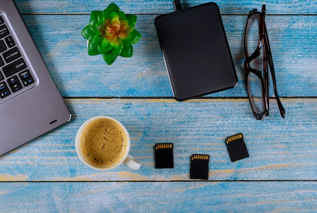 Vista superior de vasos y café, computadora portátil con disco duro externo, tarjeta sd en la mesa de madera de los fotógrafos