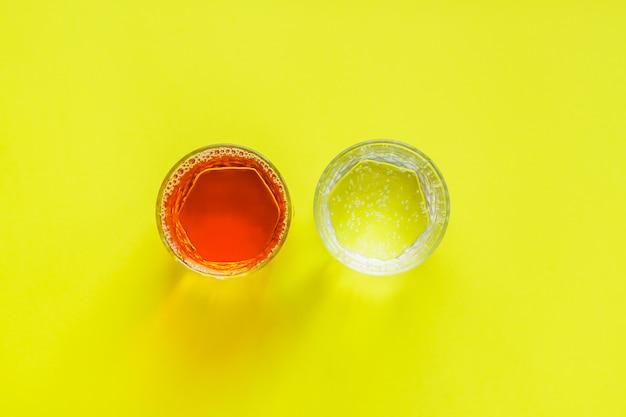 Vista superior de vasos transparentes con jugo de manzana y agua con gas sobre fondo amarillo