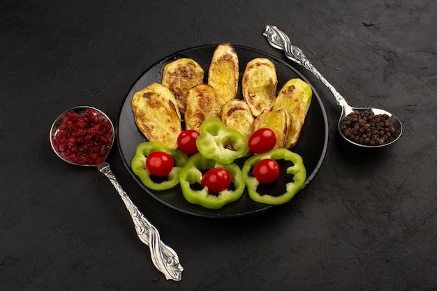 Vista superior vegetales cocidos y rebanados frescos dentro de un plato negro en la oscuridad