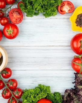 Vista superior de vegetales como tomate cilantro albahaca con pimienta negra trituradora de ajo en madera con espacio de copia