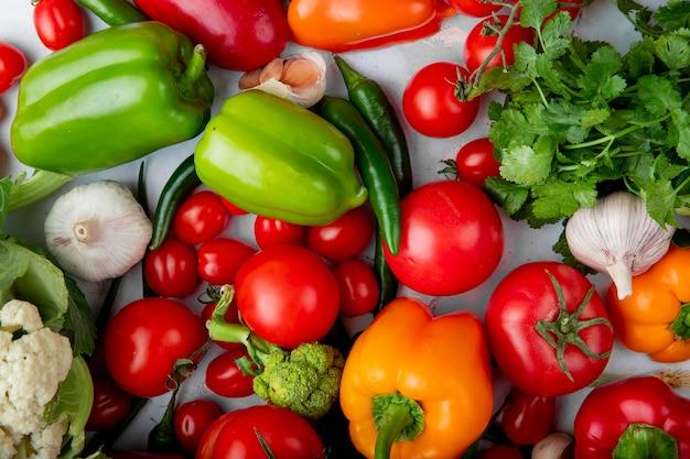 Vista superior de vegetales frescos maduros como tomates coloridos pimientos ají verde ajo cebolla verde y brócoli sobre fondo blanco.