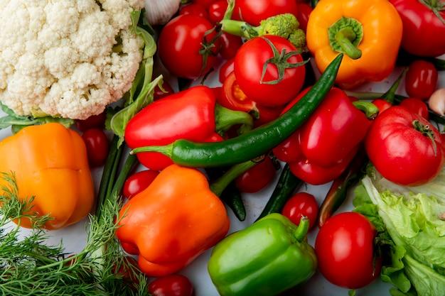 Vista superior de vegetales frescos maduros tomates ají verde coloridos pimientos ajo brócoli y coliflor sobre fondo de mármol