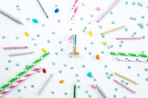 Una vista superior de velas y dulces decoraciones de cumpleaños en el escritorio blanco, celebración de la fiesta de cumpleaños