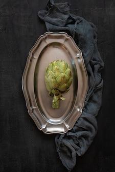 Vista superior de verde de alcachofa fresca en plato de metal