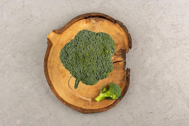 Vista superior verde brócoli fresco maduro sobre el fondo gris