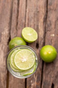 Vista superior verde lima en rodajas en el agua de soda y lugar de vidrio en la mesa de madera
