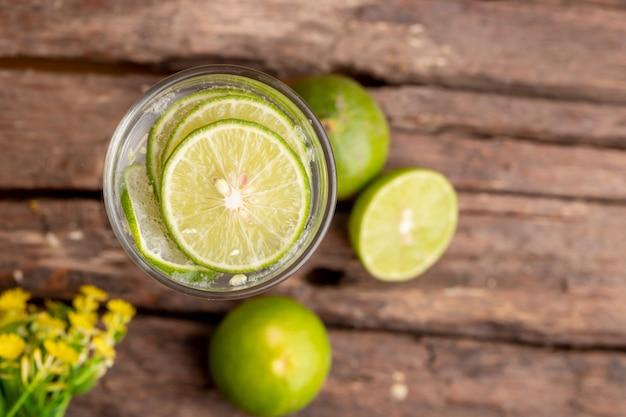 Vista superior verde lima en rodajas en el lugar de vidrio y agua de soda en la mesa de madera con flores amarillas