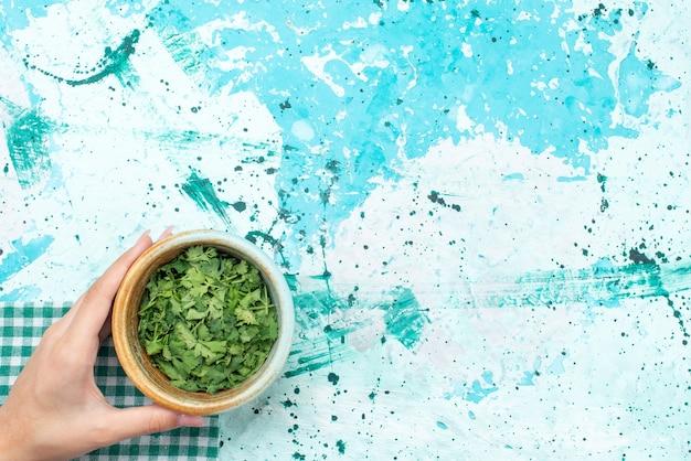 Vista superior de los verdes dentro del recipiente en azul, ingrediente de comida verde