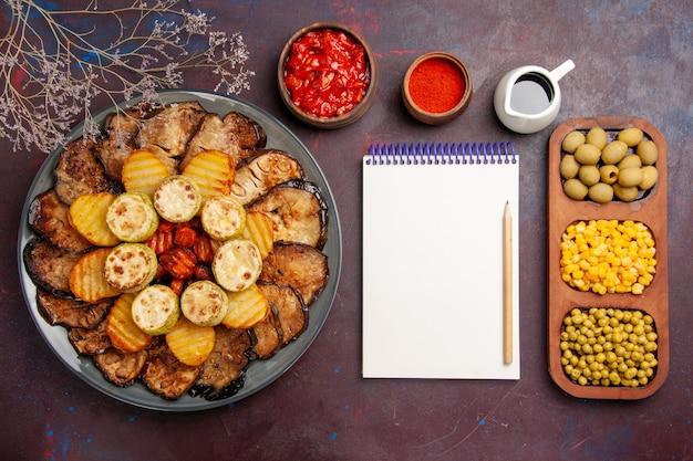Vista superior de verduras al horno sabrosas patatas y berenjenas en el horno de comida de fondo oscuro cocinar verduras hornear