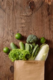 Vista superior de verduras en bolsa de compras en mesa de madera