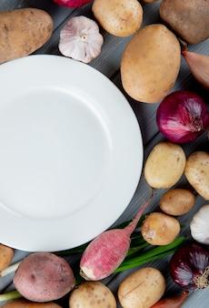 Vista superior de verduras como el ajo rábano cebolla de patata con plato vacío sobre fondo de madera