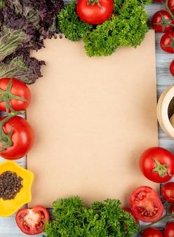 Vista superior de verduras como albahaca tomate cilantro con pimienta negra y trituradora de ajo con bloc de notas sobre superficie de madera con espacio de copia