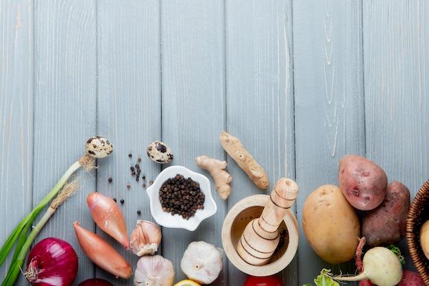 Vista superior de verduras como cebolla patata huevo ajo jengibre con pimienta negra y trituradora de ajo sobre fondo de madera con espacio de copia
