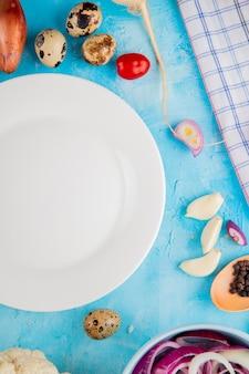 Vista superior de verduras como huevo de cebolla ajo con plato vacío sobre fondo azul.