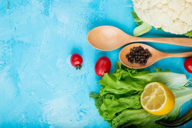 Vista superior de verduras como lechuga, tomate, coliflor con especias de limón y pimienta sobre superficie azul