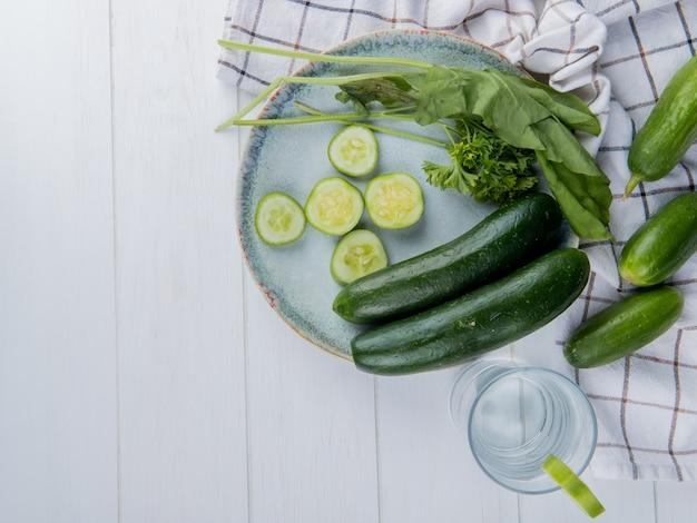 Vista superior de las verduras como pepino entero y en rodajas de espinacas y cilantro con pepinos sobre tela y desintoxicación de agua sobre madera con espacio de copia