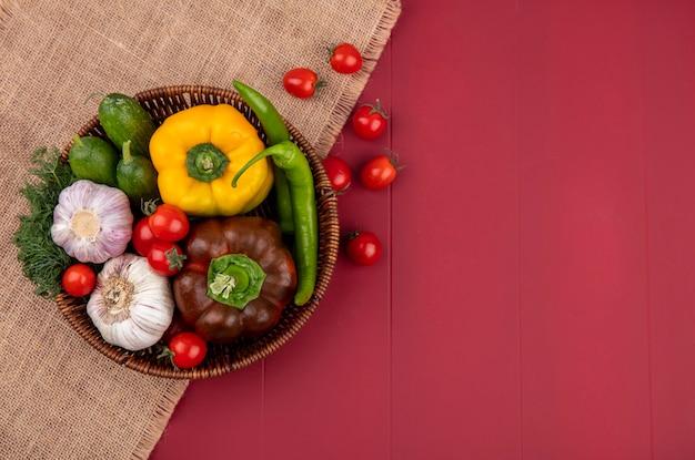 Vista superior de verduras como pimiento pepino tomate ajo eneldo en canasta de cilicio y superficie roja