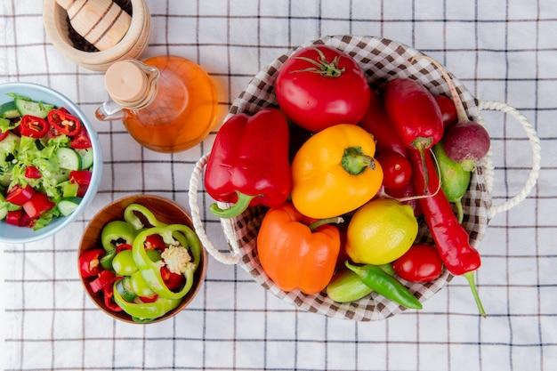 Vista superior de verduras como pimiento, tomate, pepino en una cesta con ensalada de verduras, mantequilla derretida y trituradora de ajo sobre una superficie de tela escocesa