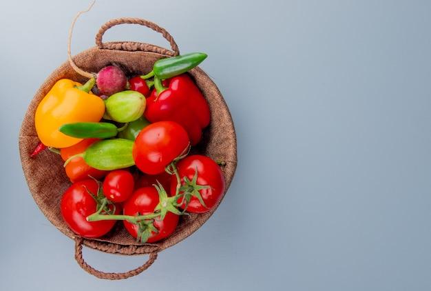 Vista superior de verduras como rábano tomate pimiento en la cesta en el lado izquierdo y fondo azul con espacio de copia