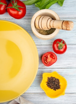 Vista superior de verduras como tomate hojas de menta verde con semillas de pimienta negra trituradora de ajo y plato vacío sobre superficie de madera