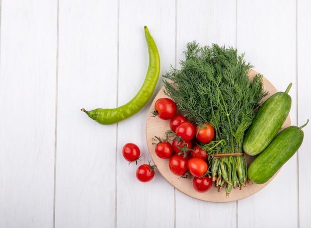 Vista superior de verduras como tomate pepino y eneldo en tabla de cortar con pimiento sobre superficie de madera