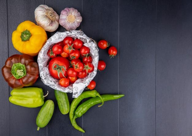 Vista superior de verduras como tomates en la cesta pepinos pimientos bulbos de ajo en superficie negra