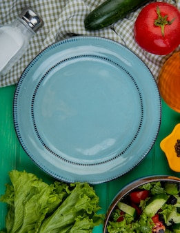 Vista superior de verduras cortadas y enteras como lechuga pepino albahaca tomate con sal pimienta negra y plato vacío sobre superficie verde
