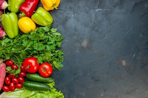 Vista superior de verduras de diferentes colores pimientos tomates cherry pepinos lechuga rábano limón perejil tomates en la mesa oscura espacio libre