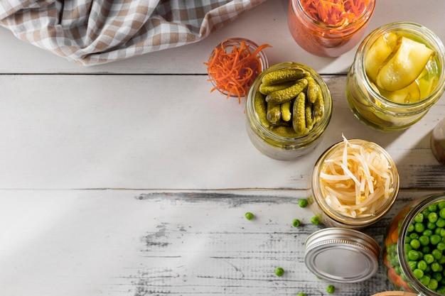 Vista superior de verduras encurtidas en frascos transparentes con espacio de copia