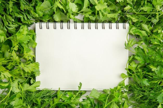 Vista superior de verduras frescas con bloc de notas sobre fondo blanco.