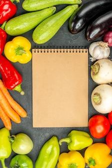 Vista superior de verduras frescas con bloc de notas sobre fondo oscuro