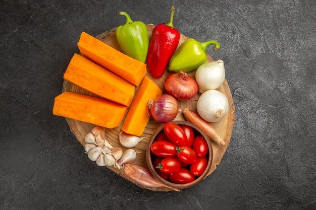 Vista superior de verduras frescas con calabaza en rodajas sobre el fondo gris oscuro color maduro fresco