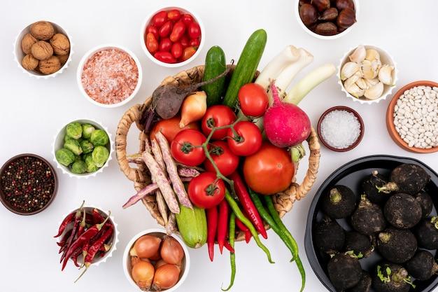 Vista superior de verduras frescas en la cesta rodeada de otros vegetales en platos y tazones blancos sobre blanco