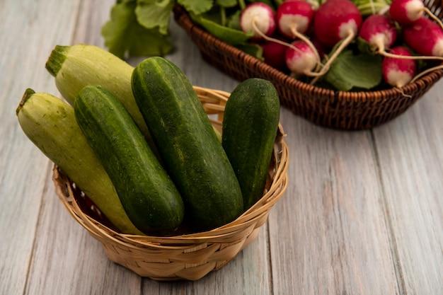 Vista superior de verduras frescas como pepinos y calabacines en un balde con rábanos en un balde sobre una pared de madera gris