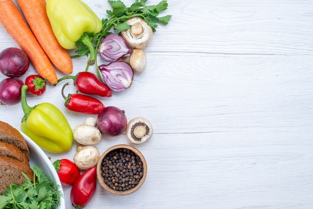 Vista superior de verduras frescas como pimiento, zanahoria, cebolla con pan en la mesa de luz, comida vegetal, plato de vitamina