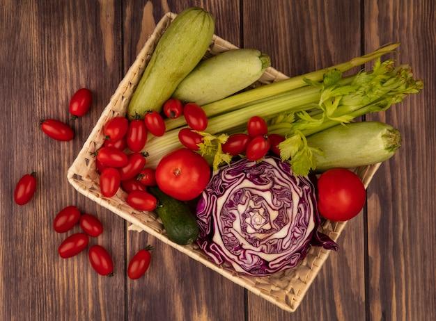 Vista superior de verduras frescas como tomates, apio, repollo morado y calabacines en un balde sobre un fondo de madera