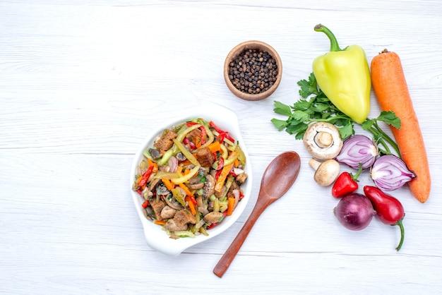 Vista superior de verduras frescas como zanahoria, cebollas y pimiento verde con rodajas de carne en una comida ligera, vegetal, vitamina
