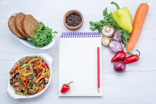 Vista superior de verduras frescas como zanahoria, cebollas y pimiento verde con rodajas de carne en un piso ligero, comida vegetal, carne de vitamina