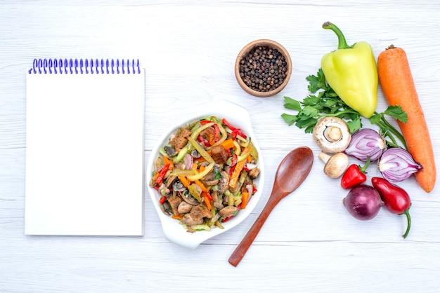 Vista superior de verduras frescas como zanahoria, cebollas verdes y pimiento verde con rodajas de carne en una comida ligera, vegetal, vitamina, carne