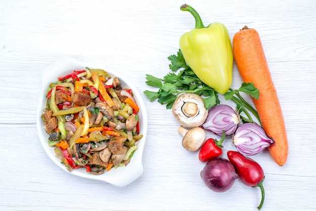 Vista superior de verduras frescas como zanahoria, cebollas verdes y pimiento verde con rodajas de carne en un escritorio de luz, comida vegetal vitamina