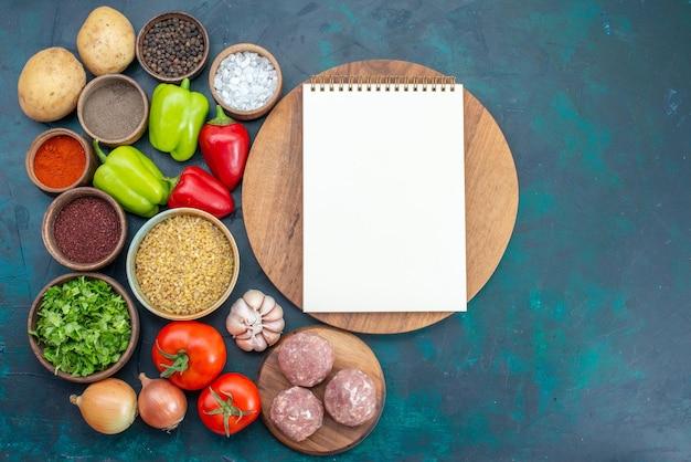 Vista superior de verduras frescas con condimentos, carne y verduras en el escritorio azul oscuro
