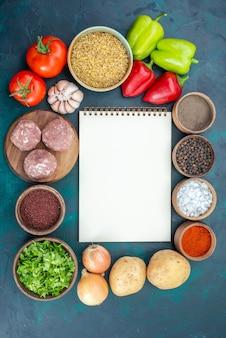 Vista superior de verduras frescas con condimentos, carne y verduras en la superficie azul oscuro