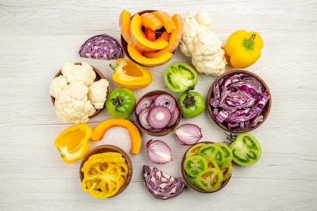 Vista superior verduras frescas cortadas tomates verdes cortados repollo rojo cortado cebolla cortada calabaza coliflor cortada pimiento en tazones sobre mesa de madera blanca